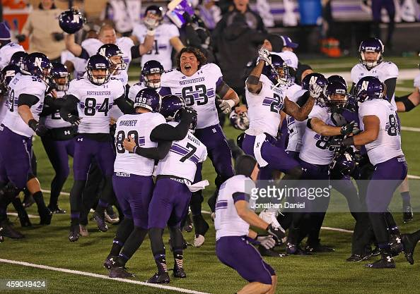 Members of the Northwestern Wildcats celebrate an overtime win against the Notre Dame Fighting Irish at Notre Dame Stadium on November 15 2014 in...