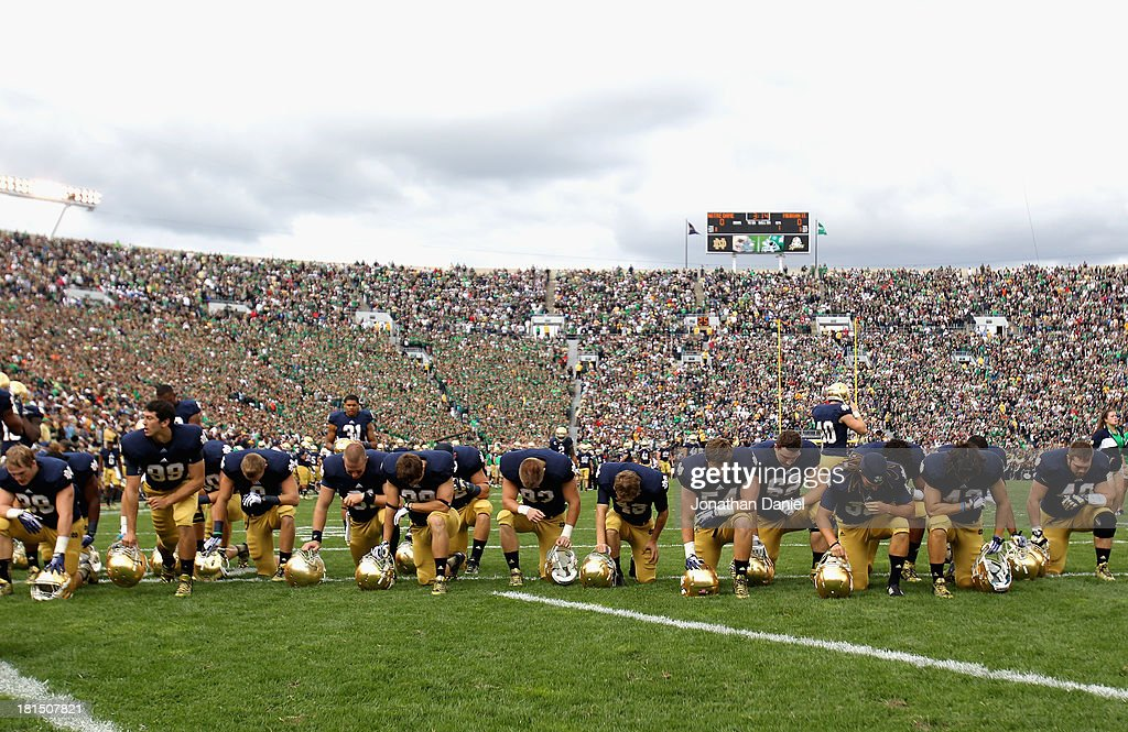 Members of the Notre Dame Fighting Irish pray before a game against the Michigan State Spartans at Notre Dame Stadium on September 21, 2013 in South Bend, Indiana. Notre Dame defeated Michigan State 17-13.