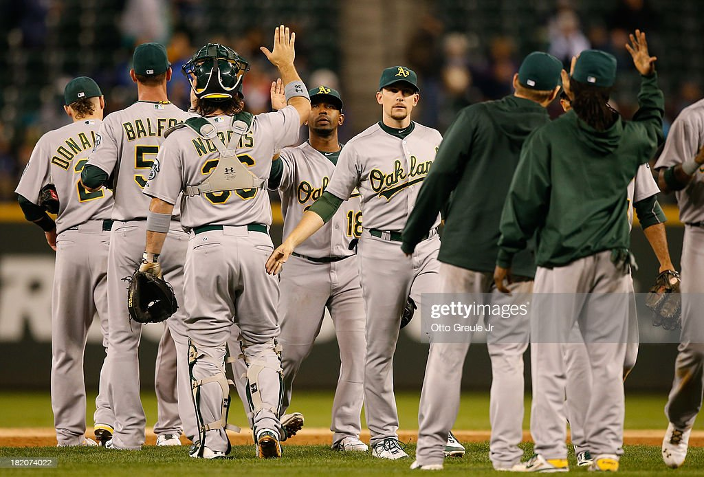 Members of the Oakland Athletics celebrate after defeating the Seattle Mariners 8-2 at Safeco Field on September 27, 2013 in Seattle, Washington.