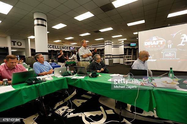 Members of the Oakland Athletics draft team watch as the Athletics draft is announced on TV in the Athletics draft room during the first day of the...