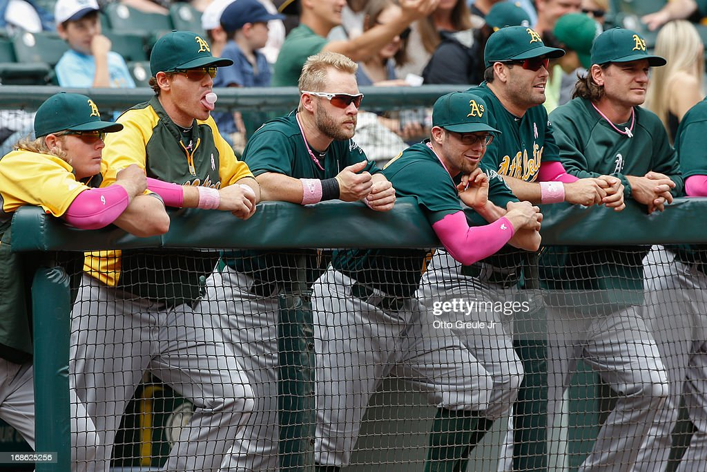 Members of the Oakland Athletics, dressed partially in pink to help raise awareness for breast cancer, watch from the dugout during the game against the Seattle Mariners at Safeco Field on May 12, 2013 in Seattle, Washington.