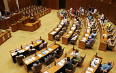 Members of the Okinawa prefectural assembly stand to approve a statement calling on the central government to stop construction of helipads in the US...