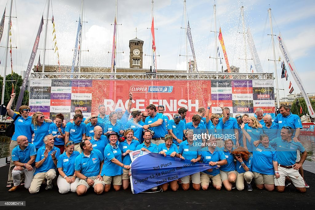 Members of the One DLL yacht crew celebrate in Saint Katherine's Dock in London, England after taking the third position in the 2013-14 Clipper Round the World Yacht Race, on July 12, 2014. The world's longest ocean race began on September 1, 2013, with a 12-strong fleet visiting 14 ports on six continents and travelling 40,000 miles before returning to the British capital. AFP PHOTO/Leon Neal