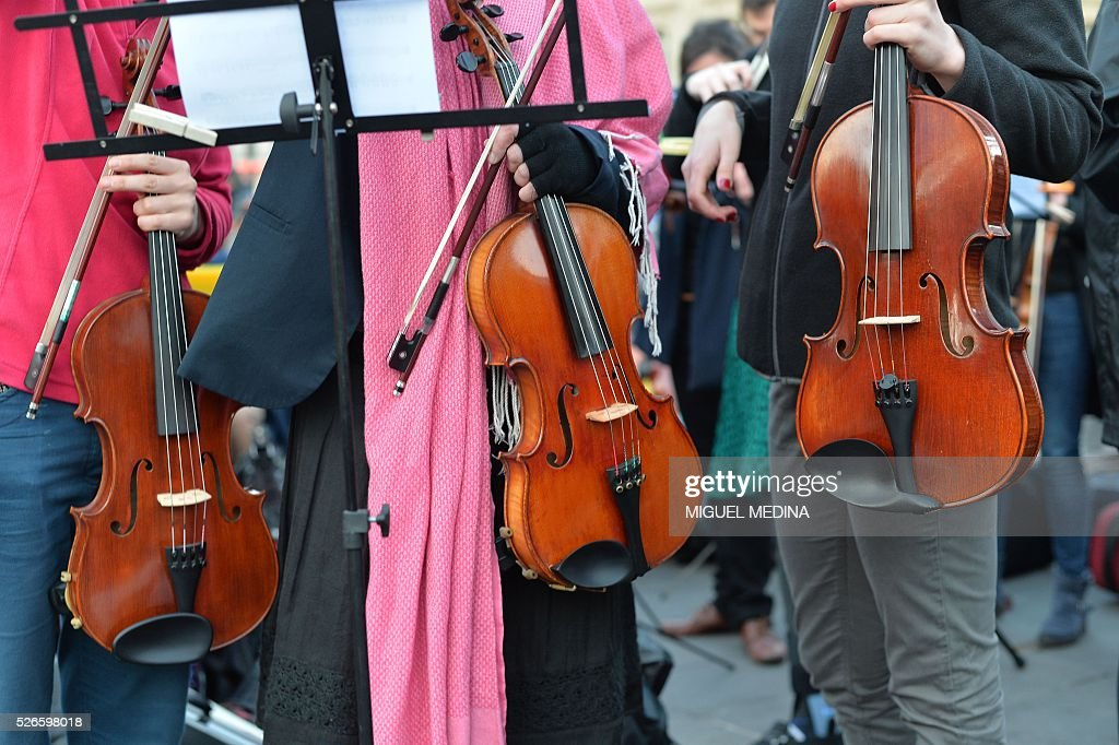 Members of the orchestra of classical music 'Standing Musicians' hold their violins during a rehearsal prior a concert at the Place de la Republique in Paris during the 'Nuit Debout' (Up All Night) movement against the French government's proposed labour reforms on April 30, 2016. / AFP / MIGUEL