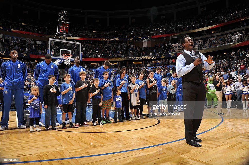 Members of the Orlando Magic and children listen to the National Anthem prior to the New Orleans Hornets , Orlando Magic game on December 26, 2012 at Amway Center in Orlando, Florida.