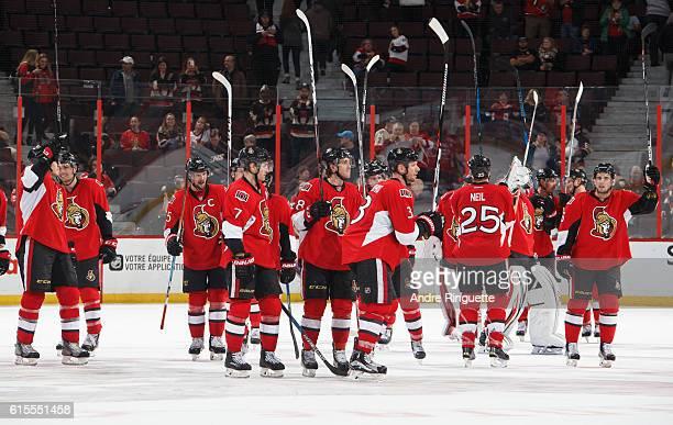 Members of the Ottawa Senators including Erik Karlsson Kyle Turris Mike Hoffman Marc Methot Chris Neil and Chris Wideman raise their sticks to salute...