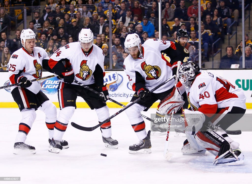 Members of the Ottawa Senators including <a gi-track='captionPersonalityLinkClicked' href=/galleries/search?phrase=Robin+Lehner&family=editorial&specificpeople=5894610 ng-click='$event.stopPropagation()'>Robin Lehner</a> #40, <a gi-track='captionPersonalityLinkClicked' href=/galleries/search?phrase=Eric+Gryba&family=editorial&specificpeople=570539 ng-click='$event.stopPropagation()'>Eric Gryba</a> #62, <a gi-track='captionPersonalityLinkClicked' href=/galleries/search?phrase=Colin+Greening&family=editorial&specificpeople=7183741 ng-click='$event.stopPropagation()'>Colin Greening</a> #14, and Chris Neil #25, watch a loose puck in front of the net against the Boston Bruins in the first period during the game at TD Garden on December 27, 2013 in Boston, Massachusetts.
