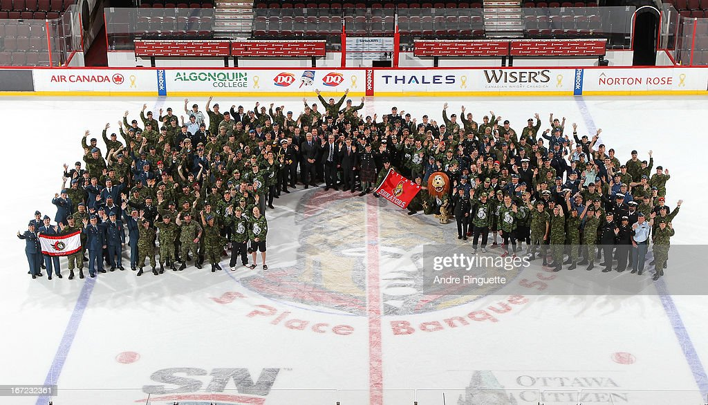 Members of the Ottawa Senators pose for a picture at center ice with military personnel on Canadian Forces Appreciation Night after a game against the Pittsburgh Penguins on April 22, 2013 at Scotiabank Place in Ottawa, Ontario, Canada.