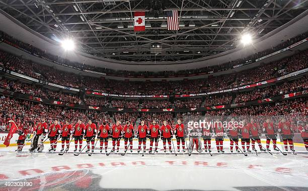 Members of the Ottawa Senators stand at attention during the singing of the national anthems prior their home opener against the Montreal Canadiens...