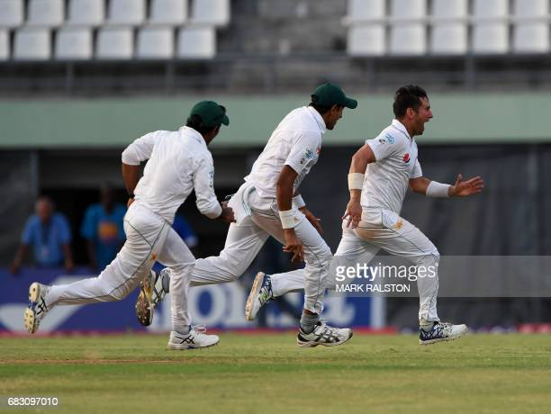 Members of the Pakistan cricket team celebrate with final wicket taker Yasir Shah after winning the final test match and the series 21 against the...