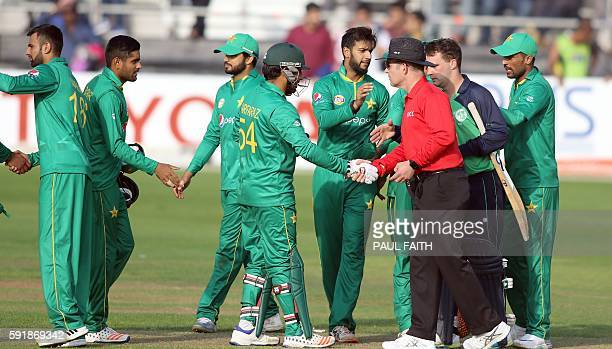 Members of the Pakistan team and Ireland's Peter Chase shake hands with the empire and their team mates after Pakistan won the first one day...