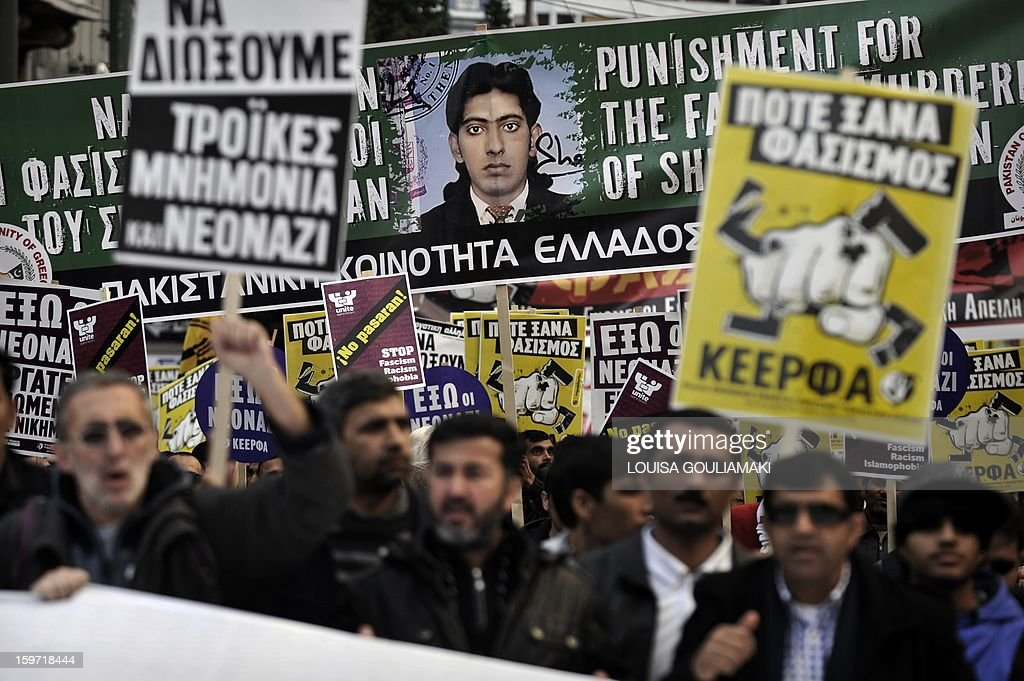Members of the Pakistani community in Athens carry a banner bearing a picture of a 27 years old Pakistani migrant victim of what appears to be a racism-fuelled crime on January 19, 2013. Hundreds of Greeks, migrants and other nationals marched peacefully against racism and fascism . Nearly 3,000 people joined the rally that was set up by municipalities, organisations, migrant communities and main opposition party radical leftists Syriza. This week, authorities arrested a 29-year-old firefighter and another Greek man aged 25 for the murder of the 27-year-old Pakistani migrant AFP PHOTO/ LOUISA GOULIAMAKI