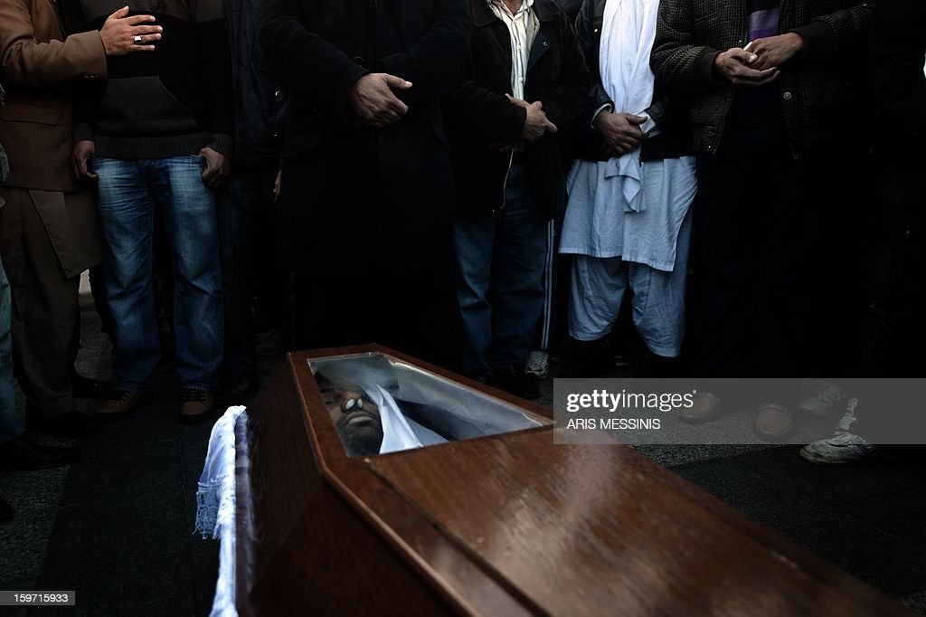 Members of the Pakistani community in Athens gather on January 19, 2013 around the coffin of a 27 years old Pakistani migrant victim of what appears to be a racism-fuelled crime. Hundreds of Greeks and other nationals marched peacefully against racism and fascism on January 19. Nearly 3,000 people joined the rally that was set up by municipalities, organisations, migrant communities and main opposition party radical leftists Syriza. This week, authorities arrested a 29-year-old firefighter and another Greek man aged 25 for the murder of the 27-year-old Pakistani migrant. AFP PHOTO / ARIS MESSINIS