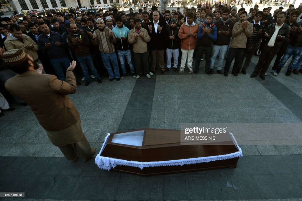 Members of the Pakistani community in Athens pray on January 19, 2013 around the coffin of a 27 years old Pakistani migrant victim of what appears to be a racism-fuelled crime. Hundreds of Greeks and other nationals marched peacefully against racism and fascism on January 19. Nearly 3,000 people joined the rally that was set up by municipalities, organisations, migrant communities and main opposition party radical leftists Syriza. This week, authorities arrested a 29-year-old firefighter and another Greek man aged 25 for the murder of the 27-year-old Pakistani migrant.