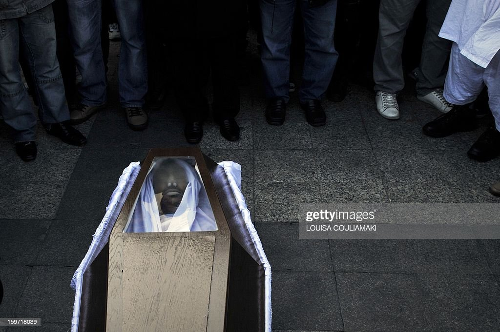 Members of the Pakistani community in Athens stand on January 19, 2013 around the coffin of a 27 years old Pakistani migrant victim of what appears to be a racism-fuelled crime. Hundreds of Greeks, migrants and other nationals marched peacefully against racism and fascism . Nearly 3,000 people joined the rally that was set up by municipalities, organisations, migrant communities and main opposition party radical leftists Syriza. This week, authorities arrested a 29-year-old firefighter and another Greek man aged 25 for the murder of the 27-year-old Pakistani migrant AFP PHOTO/ Louisa Gouliamaki
