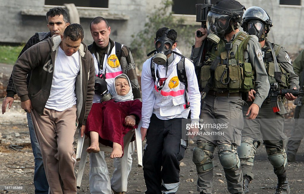 Members of the Palestinian Medical Relief Society (PMR) and volunteers carry an elderly woman who suffered from tear gas exposure while she was in her house as clashes between Israeli security forces and Palestinian protestors took place nearby, following a demonstration against the expropriation of Palestinian land by Israel on February 15, 2013, in the village of Kafr Qaddum, near the occupied West Bank city of Nablus.
