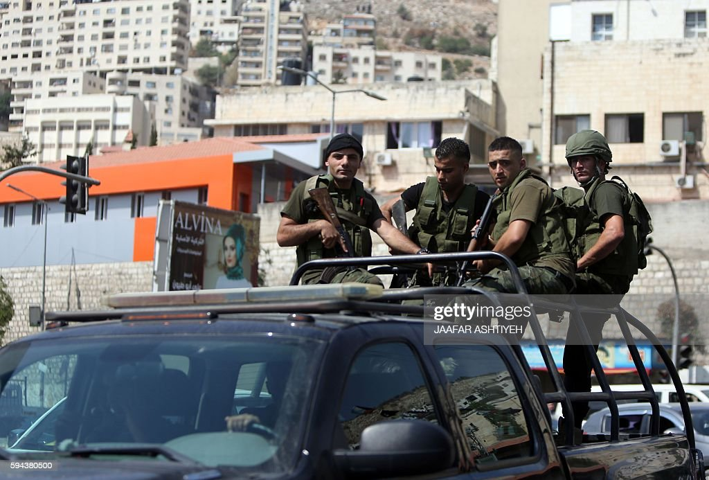Members of the Palestinian security forces stand guard patrol the West Bank city of Nablus on August 23 2016 during ongoing clashes between...