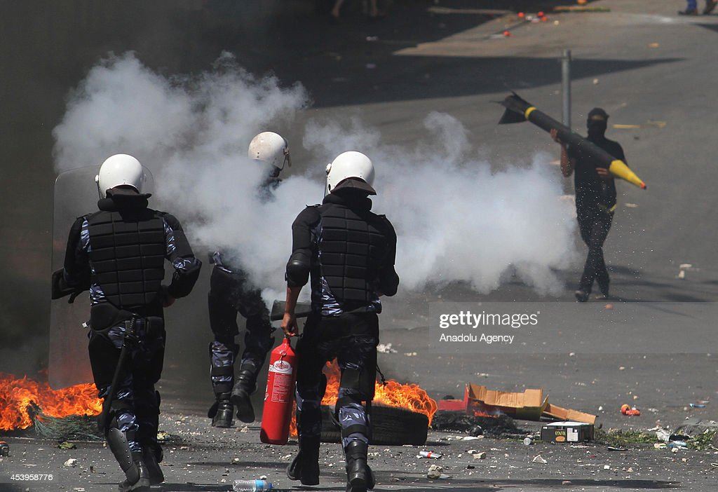 Members of the Palestinian security forces try to extinguish fire after protestors set barricades on fire following a protest to show support for resistance movement Hamas in Hebron, West Bank on August 22, 2014.