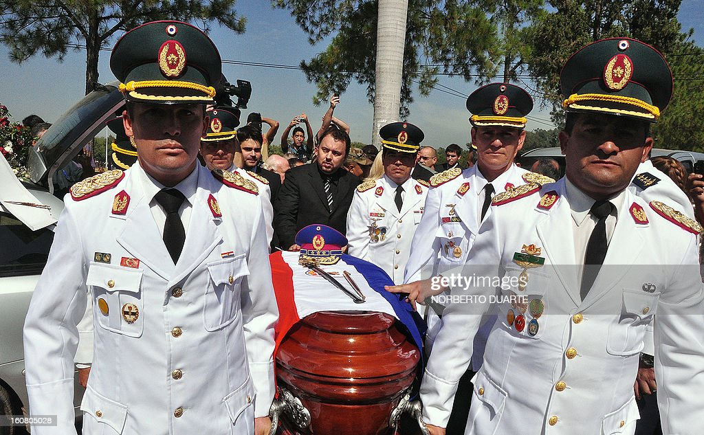 Members of the Paraguayan military carry the coffin of former general and UNACE party presidential candidate Lino Oviedo - who died along with his bodyguard Denis Galeano and pilot Ramon Picco Delmas in a helicopter crash on February 2 - in Asuncion on February 6, 2013. Oviedo, 69, the controversial presidential candidate who helped topple Paraguayan dictator Alfredo Stroessner in 1989, died when the aircraft crashed en route to Asuncion while returning from a campaign rally in northern Paraguay, prompting claims of foul play. AFP PHOTO /Norberto Duarte