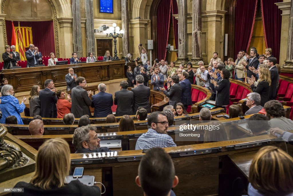 Members of the parliament applaud as Lluis Corominas, spokesman of Junts Pel Si or 'Together for Yes' party, left center, makes reference to jailed pro-independence activists Jordi Sanchez and Jordi Cuixart in Barcelona, Spain, on Thursday, Oct. 26, 2017. Catalonian President Carles Puigdemont says he won't call a regional election that could have defused tension with Spain. Photographer: Angel Garcia/Bloomberg via Getty Images