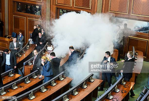 TOPSHOT Members of the Parliament disperse after a tear gas was launched by opposition lawmakers in the Kosovo's parliament in Pristina on December...