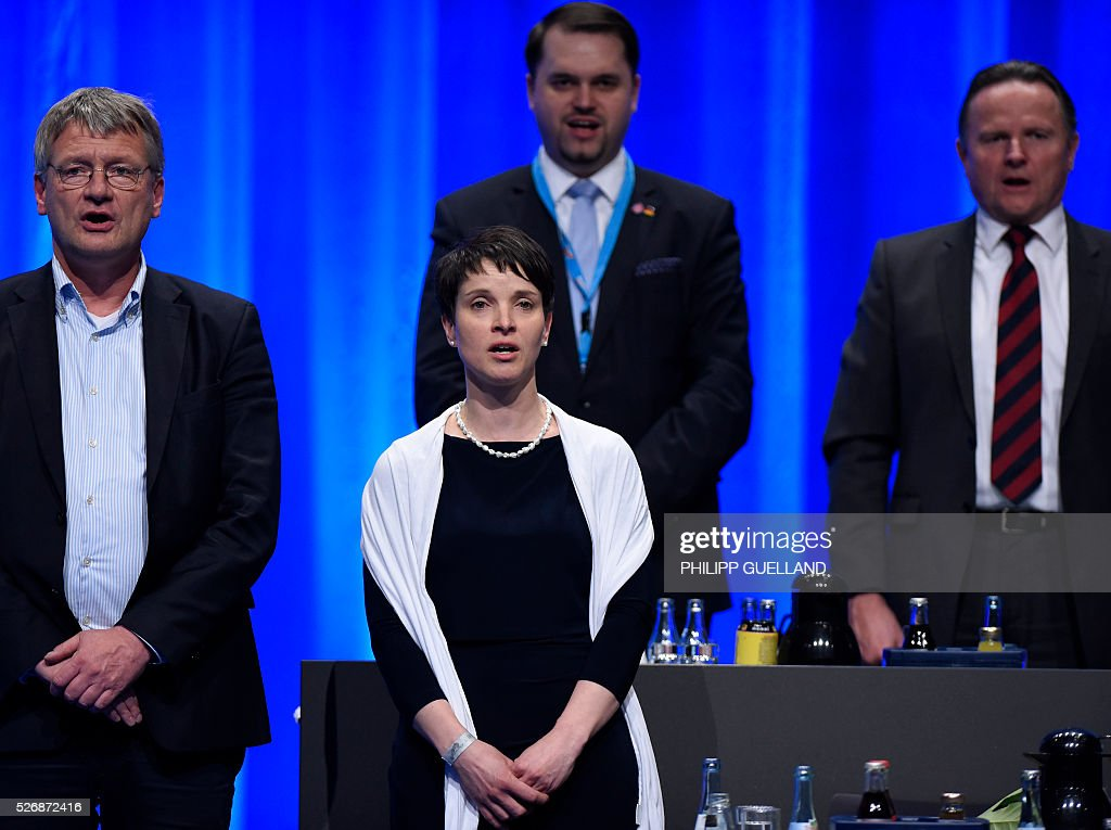 Members of the party leadership, (L-R) Joerg Meuthen, Frauke Petry, Julian Flak and Georg Pazderski sing the german national anthem at the end of the german right wing party Alternative for Germany (AfD party congress at the Stuttgart Congress Centre ICS on May 1, 2016 in Stuttgart, southern Germany. Germany's right-wing populist AfD adopted an anti-Islam policy in a manifesto that also demands curbs to immigration, as a poll showed it is now the country's third strongest party. / AFP / Philipp GUELLAND