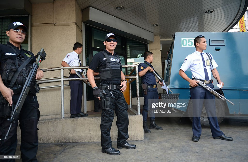 Members of the Pasay City SWAT team (L, in black) along with private security guards (R) stand guard next to an armored van in front of a bank in Manila on February 1, 2013, as part of heightened security and police visibility after recent attacks at shopping centres. Police have stepped up their visibility and security in response to recent attacks in popular Manila shopping malls, including the ransacking of a mall jewellery store on January 26.