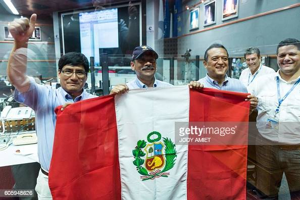 Members of the Peruvian Space Agency hold the Peru's national flag as they celebrate the success of the Vega rocket launching from the European...