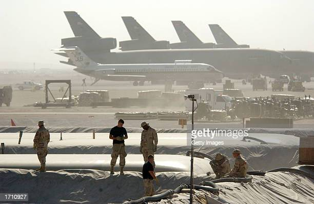 Members of the Petroleum Oils and Lubricants squadron at the 379th Air Expeditionary Wing take a break from replacing a 50000gallon fuel bladder in...