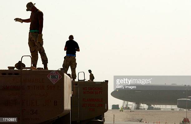 Members of the Petroleum Oils and Lubricants squadron at the 379th Air Expeditionary check the fuel levels of their trucks on December 30 2002 in Al...
