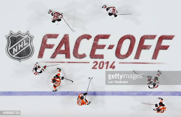 Members of the Philadelphia Flyers and the New Jersey Devils skate across the NHL FaceOff 2014 logo on October 9 2014 at the Wells Fargo Center in...