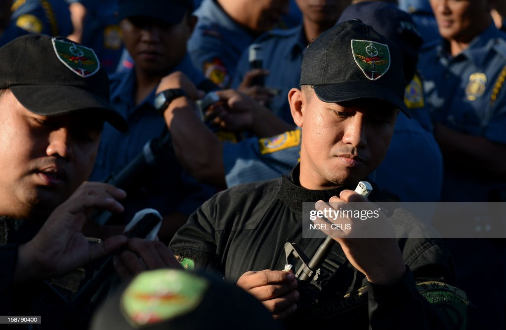 Members of the Philippine National Police (PNP) force seal the muzzles of their guns with tape in Manila on December 29, 2012, to prevent any stray gunfire that has plagued the country every New Year's Day. The taping is supposed to ensure that any policeman who fires his gun into the air on New Year's eve will be discovered, the national police chief said. AFP PHOTO / NOEL CELIS