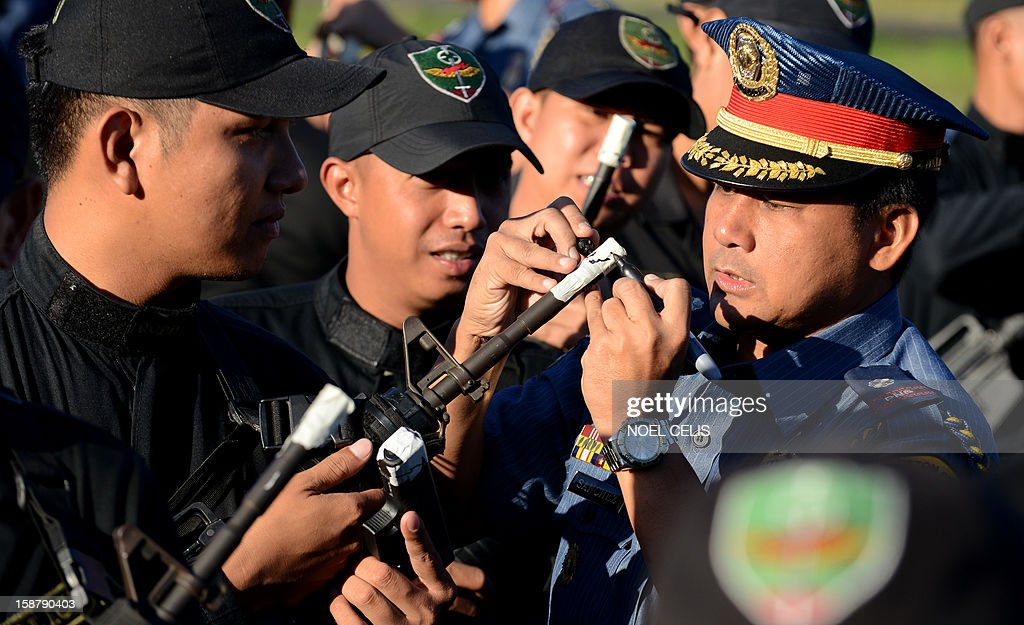 Members of the Philippine National Police (PNP) force seal the muzzles of their guns with tape in Manila on December 29, 2012, to prevent any stray gunfire that has plagued the country every New Year's Day. The taping is supposed to ensure that any policeman who fires his gun into the air on New Year's eve will be discovered, the national police chief said.