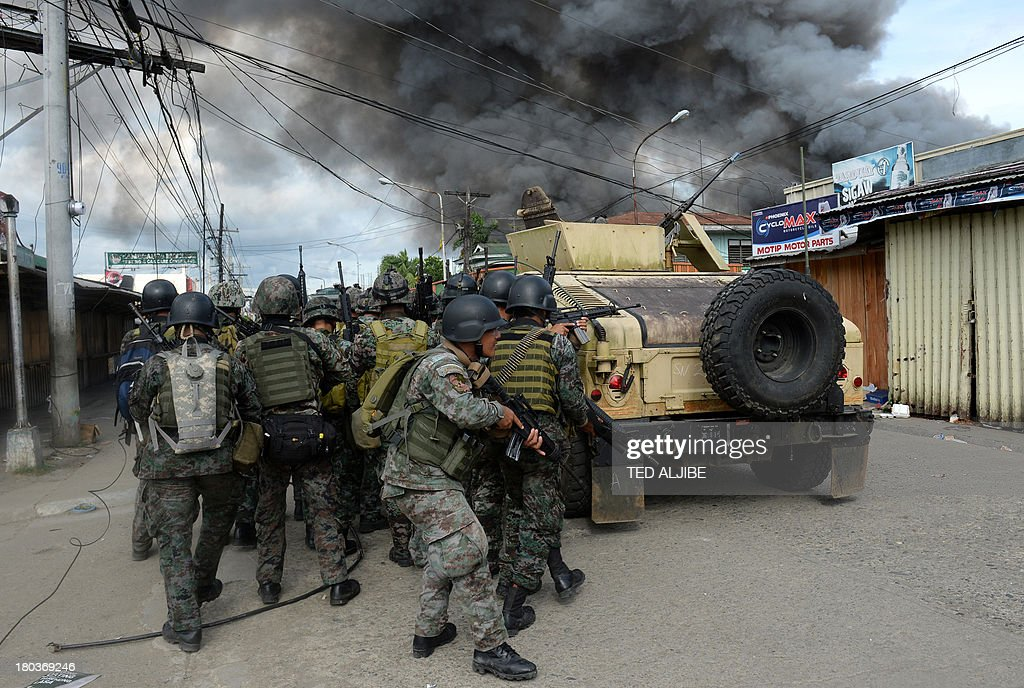 Members of the Philippine national police special forces take cover as they move forward to enemy positions among burning houses during a fire fight...