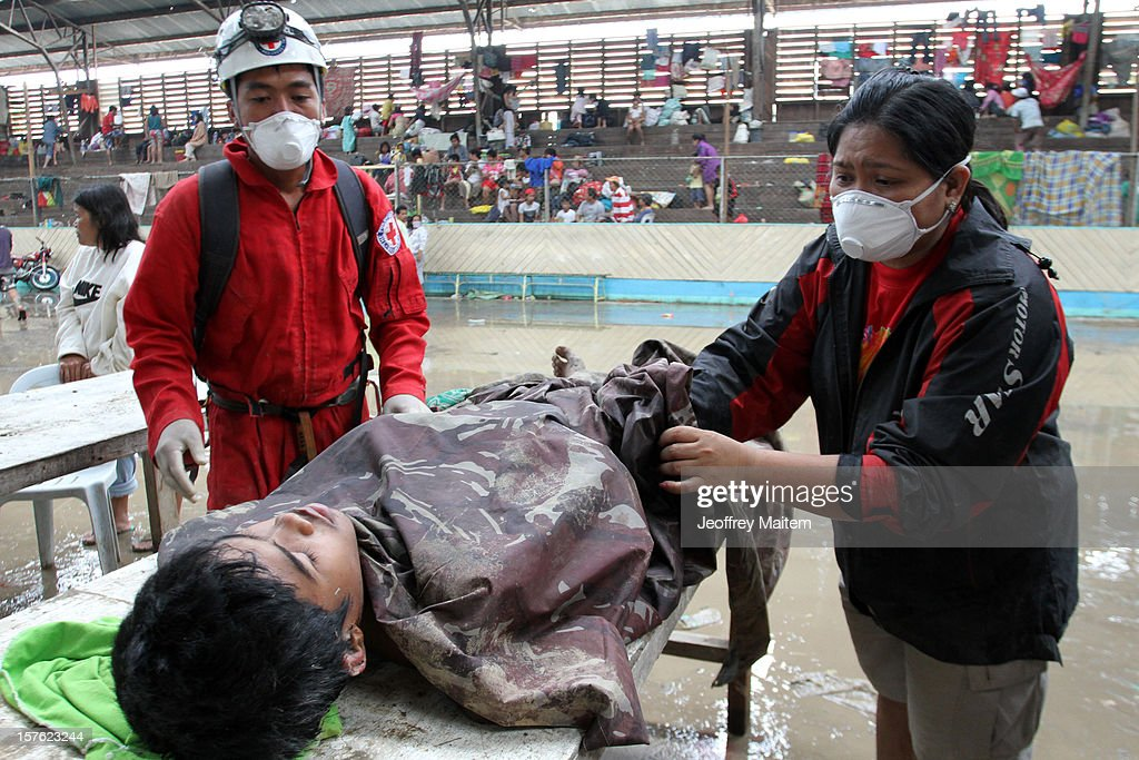 Members of the Philippine National red Cross provide first aid to a flood survivor on December 5, 2012 in the southern Philippine township of New Bataan, Compostela province, Philippines. More than 100 people have been killed and scores of others remain missing after Typhoon Bopha, the strongest storm to hit the Philippines this year, pounded the region.