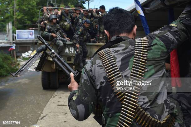 Members of the Philippine police special action force make their way to the frontline in Marawi on the southern island of Mindanao on June 19 as the...