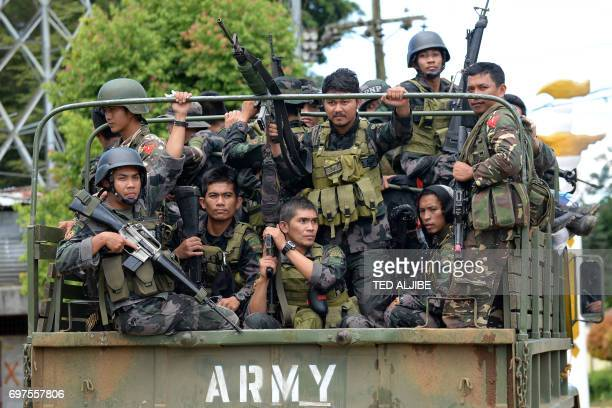 Members of the Philippine police special action force ride in an army truck on their way to the frontline in Marawi on the southern island of...