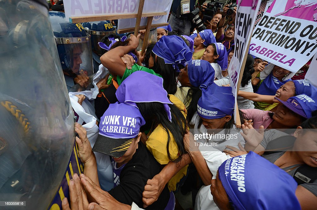 Members of the Philippine women's group Gabriela try to break a police line as they attempt to march to the US embassy for a rally in Manila on March 8, 2013. The protest march by the Philippine's women group Gabriela was held as part of International Women's Day. AFP PHOTO/TED ALJIBE