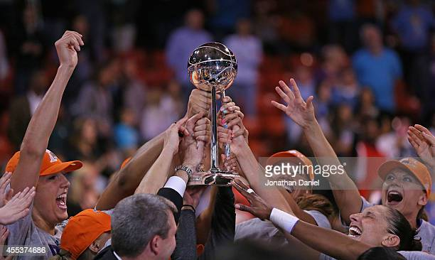 Members of the Phoenix Mercury hold the championship trophy after a win over the Chicago Sky during game three of the WNBA Finals at the UIC Pavilion...