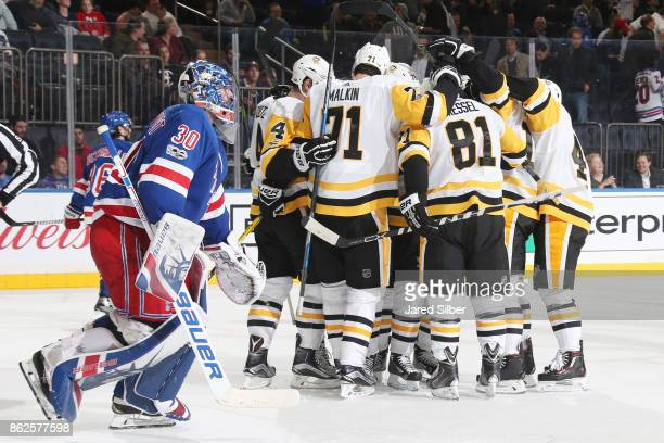 Members of the Pittsburgh Penguins celebrate an overtime goal by Evgeni Malkin as Henrik Lundqvist of the New York Rangers exits the ice at Madison...