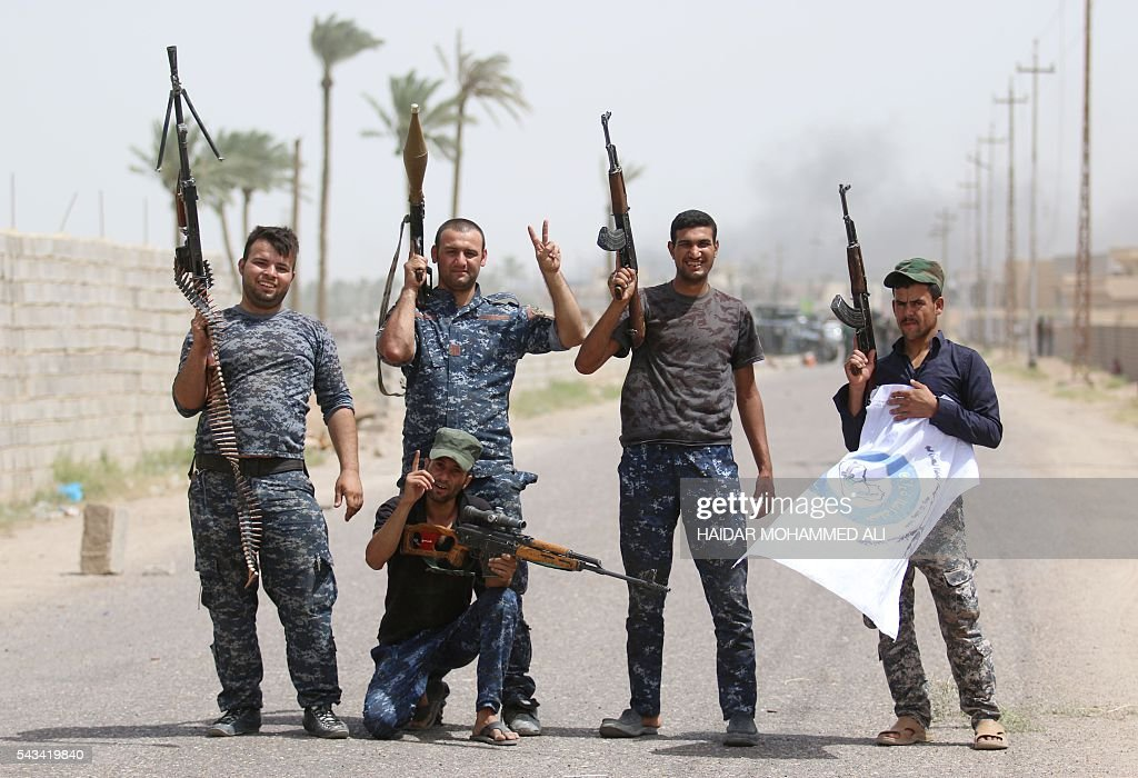 Members of the police forces pose for a photograph in Fallujah on June 28, 2016, after Iraqi forces retook the city from the Islamic State group. Iraqi forces took the Islamic State group's last positions in Fallujah on June 26, 2016, establishing full control over one of the jihadists' most emblematic bastions after a month-long operation. / AFP / HAIDAR