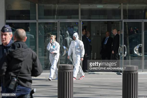 TOPSHOT Members of the POlice Forensic team leave the Paris offices of the International Monetary Fund on March 16 2017 in Paris after a letter bomb...