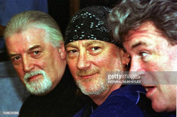 Members of the popular British rock group 'Deep Purple' Jon Lord and Roger Glover listen to fellow band member Ian Gillan speaking at a press...