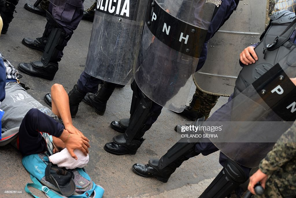 Members of the presidential honor guard and riot police stand next to a protester lying on the ground during clashes in the surroundings of the...