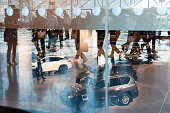 Members of the press are reflected in a window while visiting the New York International Auto Show at the Javits Center on March 24 2016 in New York...