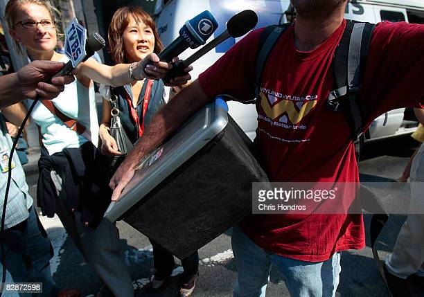 Members of the press attempt to interview an employee of Lehman Brothers Holdings Inc as he carries a box out of the company's headquarters and hails...