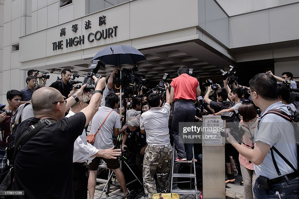 Members of the press gather to take pictures of Feng shui master Tony Chan Chun-chuen's wife Tam Miu-ching (unseen) outside the high court in Hong Kong on July 5, 2013. The former Hong Kong fortune teller who once advised Asia's richest woman was sentenced to 12 years on July 5, 2013 after a court jury found him guilty of forging her will. AFP PHOTO / Philippe Lopez