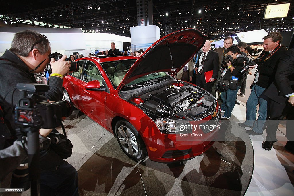 Members of the press look at the motor in Chevrolet's 2014 Cruze with a 2.0 turbo diesel at the Chicago Auto Show on February 7, 2013 in Chicago, Illinois. The Chicago Auto Show, one of the oldest and largest in the country, will be open to the public February 9-18.