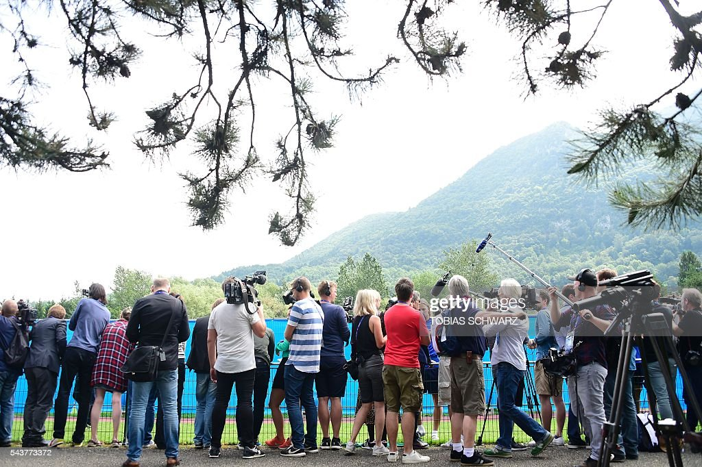Members of the press look over the fence as Iceland players take part in a training session on June 30, 2016 / AFP / TOBIAS