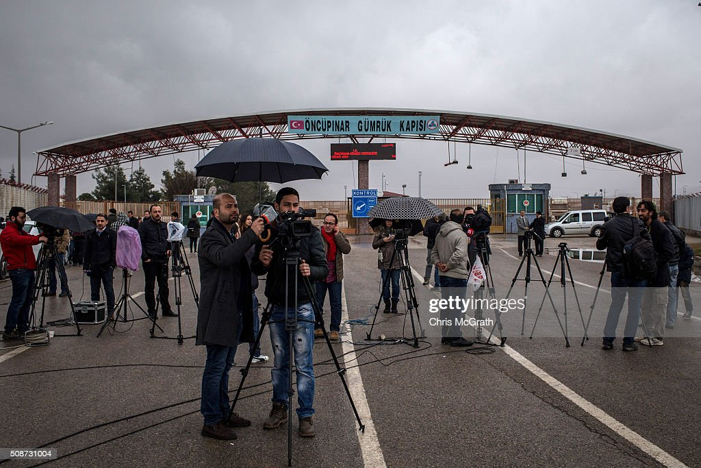 Members of the press report from in front of the closed Turkish border gate on February 6, 2016 in Kilis, Turkey. According to Turkish officials some 35,000 Syrian refugees have massed on the Syrian/Turkish border after fleeing Russian airstrikes and a regime offensive surrounding the city of Aleppo in northern Syria.